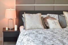 Interior de lujo del dormitorio con las almohadas y la lámpara de mesa del estampado de plores fotografía de archivo