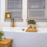Interior de relaxamento do banheiro do quadrado do quadro com o espelho branco impecável da banheira e as duas janelas foto de stock