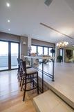 Interior de um apartamento moderno com tabela e cadeiras da barra Imagens de Stock