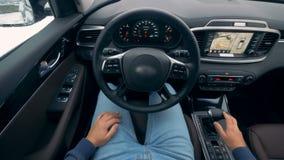 Interior de um veículo automático com um homem que senta-se para dentro Auto-conduzindo o volante de um piloto automático autônom vídeos de arquivo