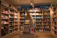 Interior de uma livraria moderna com as prateleiras de madeira completas dos livros Fotos de Stock Royalty Free