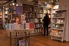 Interior de uma livraria moderna com a mulher que consulta a coleção Fotografia de Stock Royalty Free