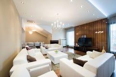 Interior de uma sala de visitas espaçoso com a chaminé no luxo apar Imagem de Stock
