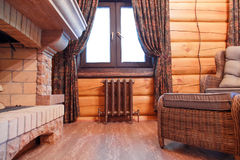 Interior de un pasillo de la chimenea en una casa de madera con un radiador retro del arrabio debajo de la ventana Imagen de archivo
