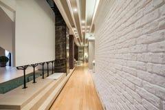 Interior de un pasillo largo con la pared de ladrillo blanca Fotografía de archivo libre de regalías