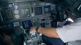 Interior de una carlinga de funcionamiento del aeroplano con los pilotos que se sientan en ella metrajes