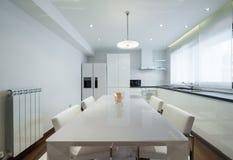 Interior de una cocina blanca brillante de lujo moderna con la cena de la etiqueta Foto de archivo