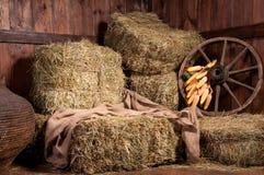 Interior de una granja rural - heno, rueda, maíz. Imagen de archivo libre de regalías