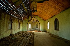 Interior of a Decaying Church. The interior of an old church is in a crumbling state of deterioration and ruins as half of the roof is without shingles Stock Photography