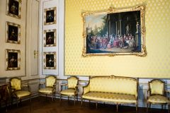 Interior decor of a stately formal salon. With upholstered wooden suite and oil paintings on the wall which is covered in matching yellow fabric to the stock photos