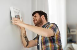 Man hanging picture in frame to wall at home. Interior decoration and renovation concept - smiling man hanging picture in frame to wall at home royalty free stock images