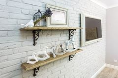 Interior decoration toys. White decorative bird near cage and ceramic horses in expensive interior stock images