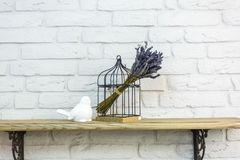 Interior decoration toys. White decorative bird near cage in expensive loft interior stock image