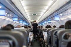 Interior del aeroplano comercial con los pasajeros de la porción de la azafata en asientos durante vuelo imagenes de archivo