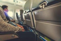 Interior del aeroplano con los pasajeros en asientos imagenes de archivo