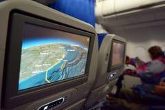 Interior del aeroplano con una ruta en un mapa de la pantalla Imagen de archivo libre de regalías