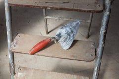 Interior del apartamento durante la renovación, el remodelado y la construcción inferiores un cuchillo de masilla en la escalera Foto de archivo libre de regalías