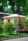 Interior del café de la calle en el parque verde de la ciudad, adornado con las flores, estación de verano, día soleado brillante Foto de archivo
