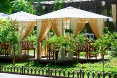Interior del café de la calle en el parque verde de la ciudad, adornado con las flores, estación de verano, día soleado brillante Fotografía de archivo libre de regalías