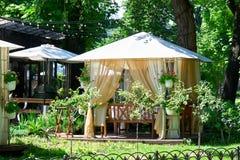 Interior del café de la calle en el parque verde de la ciudad, adornado con las flores, estación de verano, día soleado brillante Fotografía de archivo