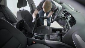 Interior del coche del hombre que limpia con la aspiradora almacen de video