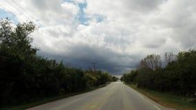 Interior del coche que conduce abajo del camino que mira en primera línea el parabrisas en un día nublado almacen de metraje de vídeo