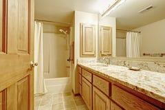 Interior del cuarto de baño con en los tonos de marfil de la suavidad con el gabinete de madera Foto de archivo
