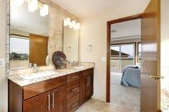 Interior del cuarto de baño con los cebinets de madera oscuros, dos fregaderos y espejos imagen de archivo