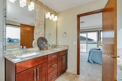 Interior del cuarto de baño con los gabinetes de madera oscuros, dos fregaderos y espejos foto de archivo libre de regalías