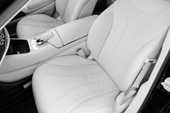 Interior del cuero blanco del coche moderno de lujo Asientos y multimedias blancos cómodos de cuero volante y tablero de instrume imágenes de archivo libres de regalías