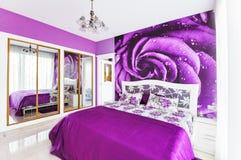 Interior del dormitorio acogedor en tonos violetas brillantes Grande duplicado Imágenes de archivo libres de regalías