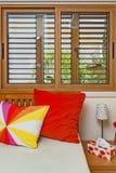 Interior del dormitorio Almohadas coloridas Ventana de madera Imágenes de archivo libres de regalías
