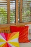 Interior del dormitorio Almohadas coloridas Ventana de madera Fotos de archivo