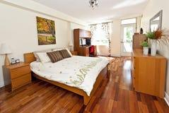 Interior del dormitorio con el suelo de madera dura Imagen de archivo libre de regalías