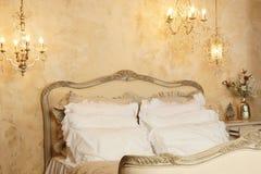 Interior del dormitorio con una cama clásica grande con las porciones de almohadas y de luces blancas en una pared beige Fotografía de archivo