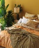 Interior del dormitorio en estilo bohemio con la cama modelada y la esquina floral foto de archivo libre de regalías