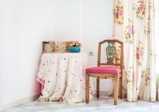 Interior del estilo del vintage con la tabla, la silla tallada y la cortina floral Foto de archivo