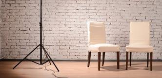 Interior del estudio con las sillas y la pared de ladrillo Imagen de archivo