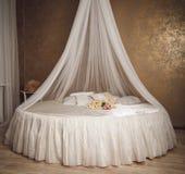 Interior del hogar con la cama blanca del círculo con el toldo Fotografía de archivo