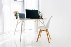 interior del lugar de trabajo con la silla, las plantas en conserva, el ordenador portátil y el ordenador fotos de archivo
