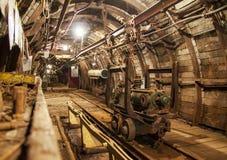 Interior del paso de la mina subterránea con los carriles, la luz y el carro Imagen de archivo