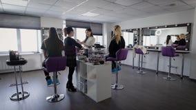 Interior del salón de belleza de lujo con dos expertos profesionales y sentarse femenino de dos modelos Los visagistes profesiona almacen de metraje de vídeo