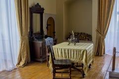 Interior del sitio de Dinning con la tabla, sillas, estatua en el castillo viejo antiguo imagen de archivo