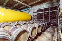 Interior del sótano con los barriles viejos del roble y cisternas del metal del lagar Foto de archivo libre de regalías
