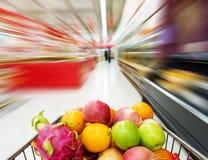 Interior del supermercado, llenado de la fruta del carro de la compra Imagenes de archivo