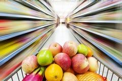 Interior del supermercado, llenado de la fruta del carro de la compra Foto de archivo libre de regalías