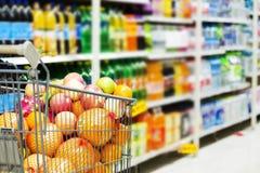 Interior del supermercado, llenado de la fruta del carro de la compra Imagen de archivo