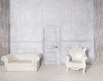 Interior del vintage con el sofá, la butaca, la pared del estuco y la puerta Foto de archivo libre de regalías