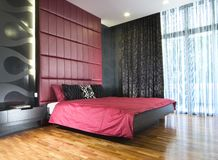 Interior design - bedroom. Master bedroom with red bedhead Stock Images