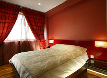 Interior design - bedroom. Master bedroom with red curtain Stock Photos